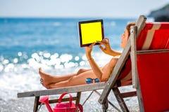 Женщина используя таблетку на sunbed Стоковые Фото