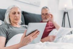 Женщина используя таблетку пока газета чтения супруга в кровати стоковое изображение
