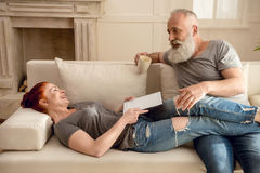 Женщина используя таблетку с кофе человека выпивая близко мимо Стоковые Фотографии RF