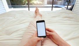 Женщина используя умный телефон на кровати Стоковая Фотография