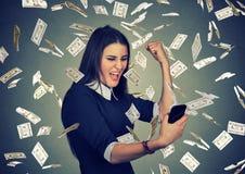 Женщина используя умный телефон под долларами дождя денег падая вниз стоковые изображения
