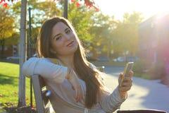 Женщина используя умный телефон, outdoors Стоковые Изображения