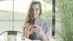 Женщина используя ходить по магазинам кредитной карточки онлайн с smartphone в кафе Счастливый для покупать акции видеоматериалы