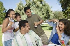 Женщина используя цифровой фотокамера фотографируя сына (13-15) с братом и сестрой отца. Стоковая Фотография