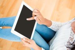 Женщина используя цифровую таблетку на поле Стоковые Изображения RF