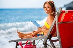 Женщина используя цифровую таблетку на sunbed Стоковое Фото