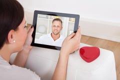 Женщина используя цифровую таблетку для онлайн датировка стоковая фотография