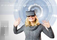 Женщина используя шлемофон виртуальной реальности против цифров произведенной предпосылки стоковые изображения rf