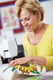 Женщина используя электрическую швейную машину Стоковые Изображения RF