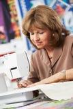 Женщина используя электрическую швейную машину Стоковое Изображение RF