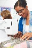 Женщина используя электрическую швейную машину Стоковые Фото