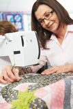 Женщина используя электрическую швейную машину Стоковые Фотографии RF