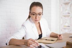 Женщина используя smartphone на таблице Стоковое Фото
