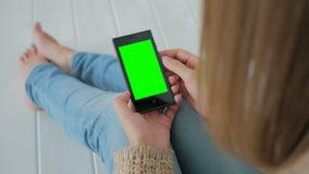 Женщина используя smartphone с зеленым экраном Стоковые Изображения RF
