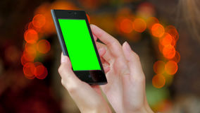 Женщина используя smartphone с зеленым экраном Стоковое фото RF