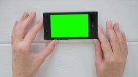 Женщина используя smartphone с зеленым экраном Стоковые Фотографии RF