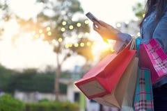 Женщина используя smartphone с хозяйственными сумками в руке Стоковое фото RF