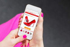 Женщина используя smartphone для того чтобы купить ботинки онлайн стоковые изображения