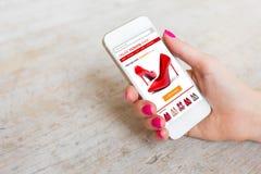 Женщина используя smartphone для того чтобы купить ботинки онлайн стоковые изображения rf