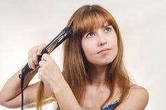 Женщина исправляет острозубцы волос Стоковые Фотографии RF