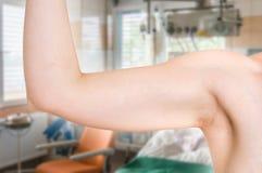 Женщина испытывает ее мышцу под ее рукой стоковое фото