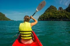 Женщина исследуя спокойного тропического залива с горами известняка каяком, задним взглядом стоковые фотографии rf