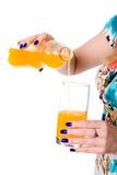 Женщина лить апельсиновый сок от бутылки в стекло Стоковая Фотография