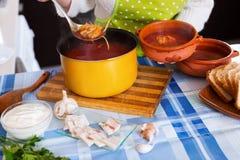 Женщина лить традиционный русский суп Стоковые Изображения RF