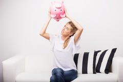 Женщина ища деньги в копилке стоковая фотография rf