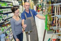 Женщина ища лопаткоулавливатель в магазине оборудования Стоковые Фото