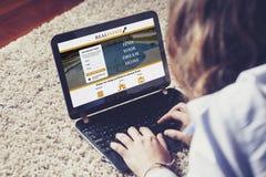 Женщина ища домой в вебсайте недвижимости с компьтер-книжкой Стоковые Фото