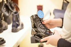 Женщина ища скидки и принимая черный ботинок с скидкой подписывает внутри магазин женщина ног принципиальной схемы мешка предпосы Стоковые Изображения RF