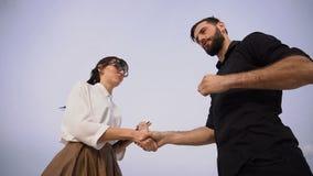 Женщина и автогонщик журналиста замедленного движения трясут руки после интервью сток-видео