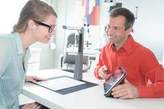Женщина и бизнесмен сидя на столе в передней таблетке Стоковая Фотография RF