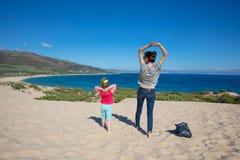 Женщина и девушка делая гимнастику поверх дюны Valdevaqueros стоковая фотография