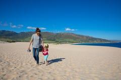 Женщина и девушка идя на песок пляжа Valdevaqueros в Кадис стоковые фотографии rf