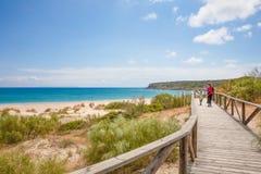 Женщина и девушка идя на footbridge на пляже в Кадис стоковое изображение