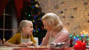 Женщина и девушка пенсионера смотря печенья Xmas и обнимая, счастливые памяти акции видеоматериалы