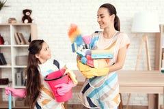 Женщина и девушка представляют с деньгами для очищать квартиру Они дома стоковые изображения rf