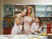 Женщина и 2 девушки делая тесто Стоковые Фотографии RF