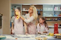 Женщина и 2 девушки делая тесто Стоковая Фотография RF