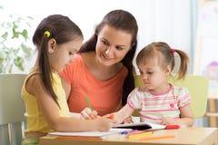Женщина и дети рисуя с покрашенными карандашами Стоковая Фотография