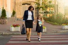 Женщина и дето- молодая школьница держа руки, на cr зебры стоковая фотография rf