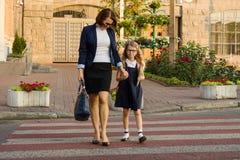 Женщина и дето- молодая школьница держа руки, на cr зебры Стоковые Изображения