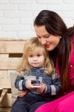 Женщина и детская игра на сотовом телефоне стоковое фото rf