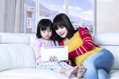 Женщина и девушка используют таблетку в живущей комнате Стоковые Изображения