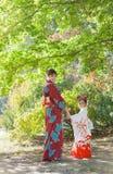 Женщина и девушка носят кимоно и идут в парк Стоковое Фото