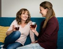 Женщина и ее дочь-подросток имея чай совместно Стоковые Изображения