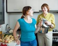 Женщина и ее зрелая мать варя еду Стоковые Фотографии RF
