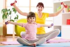 Женщина и ее дочь ребенка делая тренировки фитнеса с гантелями совместно в спортзале Стоковые Фото